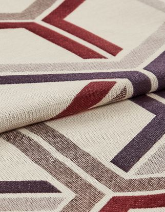 white base coloured fabric that is layered with repeating a geometric design in grey, red and purple