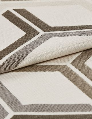 White fabric featuring a geometric design in grey and brown that repeats across the material