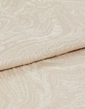 Cream and white coloured fabric in a repeating swirling pattern
