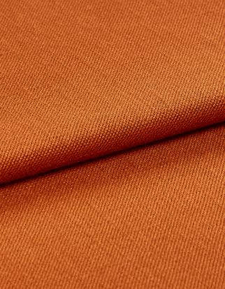 Folded over fabric that is decorated in a warm orange colour