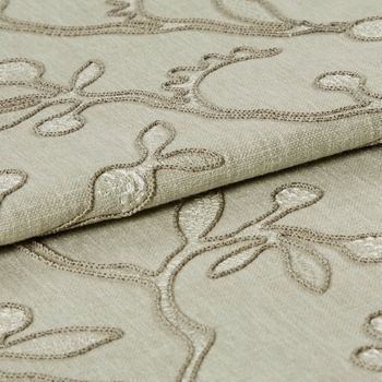 Neutral coloured fabric which has been folded is decorated with a repeating leaf and stem design