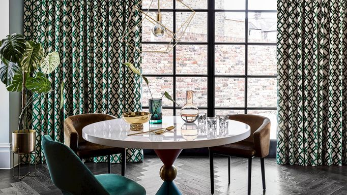 Luxe dining room with crittall doors and green geometric print curtains