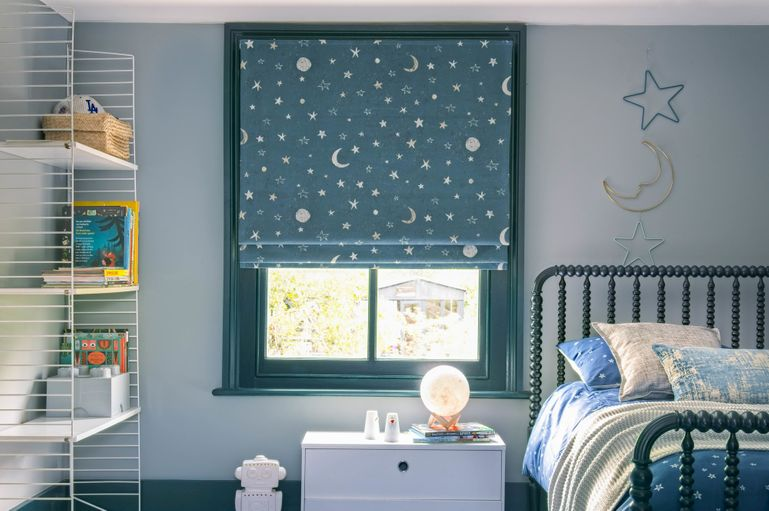 Blackout roman blinds in a bedroom window with moon and stars pattern