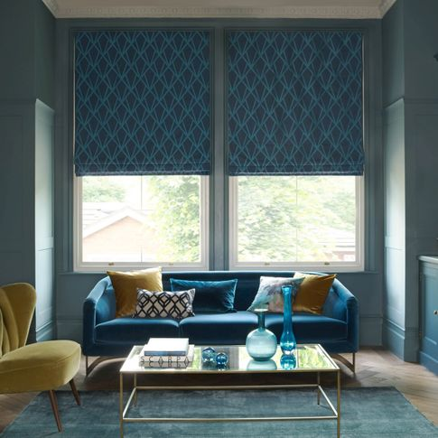 A blue room features a large window covered by a blue Roman blind that has a diamond shaped pattern. It hangs behind a blue sofa and a yellow velvet chair