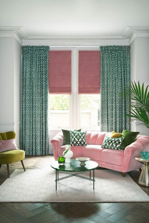 This white room features a pair of full length curtains in a green and white diamond pattern design over a pink Roman blind.