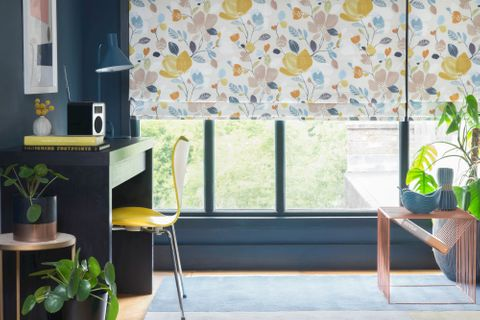 A multi-coloured floral Roman blind hangs neatly in front of a window on a petrol blue wall. Plants are dotted around the room and there is a desk to the left of the window.