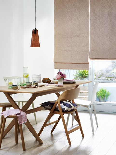 A dining room table with chairs featuring a roman blind in the background
