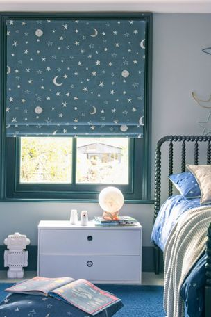 A child's bedroom with a blue roman blind featuring stars and moons. A star and moon decoration hangs on the right above the bed.