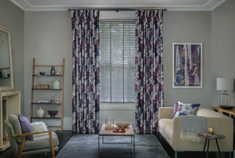 Living room with purple floral curtains layered over faux wood blinds