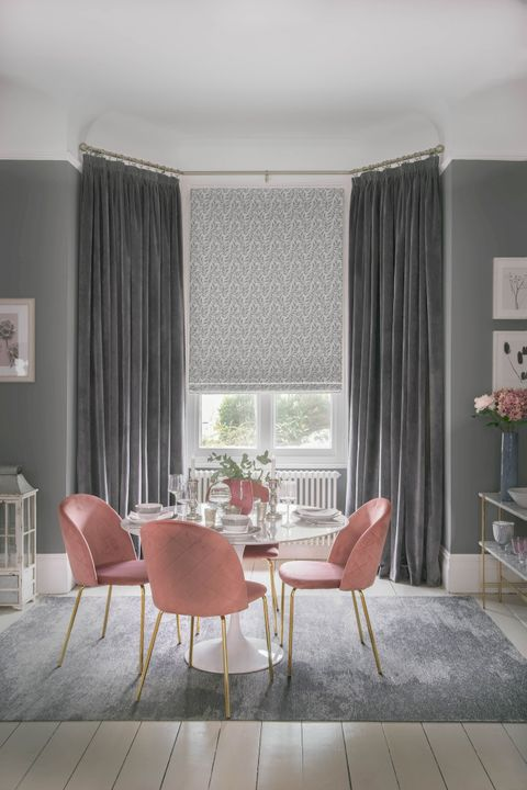 Elegant dining room with bay window featuring grey velvet curtains and a floral Roman blind