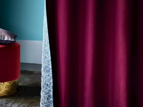Blue and white decorated curtain in a repeating geometric style with a red inner lining