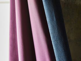 Dark blue geometric styled curtains with a purple inner lining for contrast