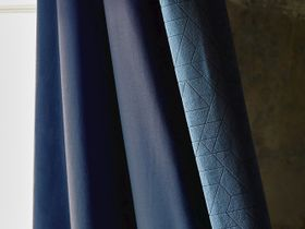 Blue curtain with a repeating geometric design and a dark blue inner layer