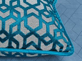 Shiny teal blue cushion with a repeating geometric pattern and light blue piped edge