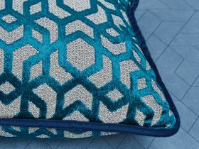 Cushions decorated with shiny teal and grey geometric pattern along with a dark blue piped edge