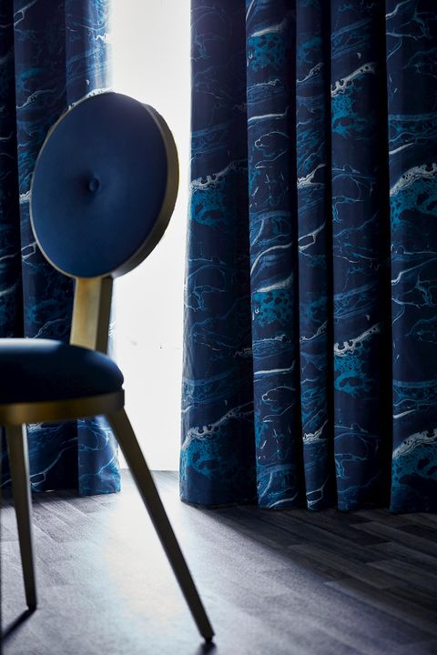 Close up detail of Onyx Magma curtains with navy blue chair