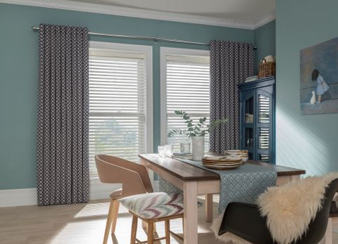 Dining room with single window dressed in Faux-wood blinds and navy blue curtains
