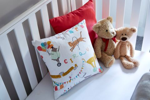 a cot decorated with teddy bears and circus patterned cushion