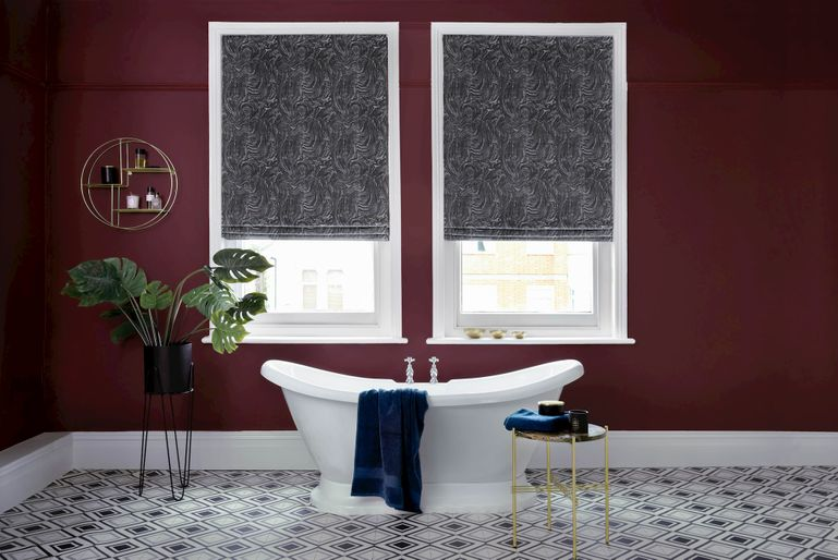Black Roman blind in a dark red luxe bathroom