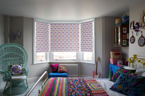 Jazz Fuchsia roller blind in a bedroom bay window