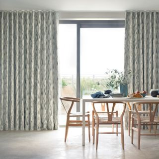 bifold doors of a dining room dressed with print pattern cream curtains