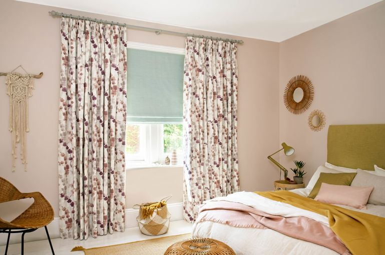 eggshell blue roman blinds and white and pink flowery curtains in a bedroom window