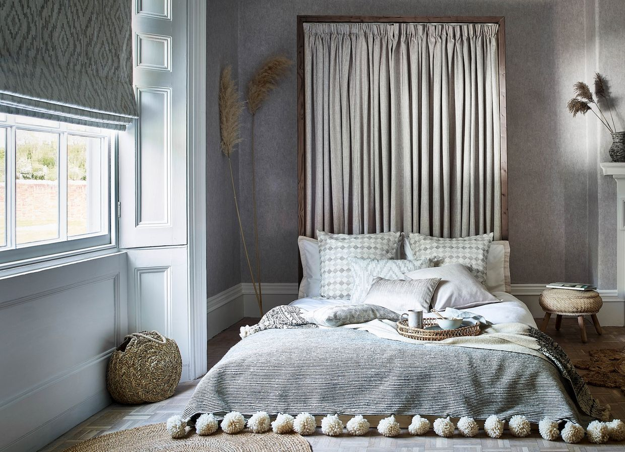 Minimalist grey bedroom with mattress on the floor and a Roman Blind in the window