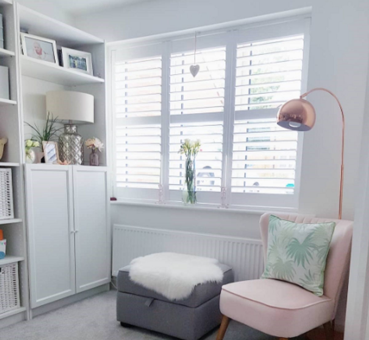 white shutters in a small window with a pink chair and lamp