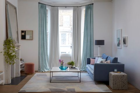 Two sets of pastel curtains in a living room. One of the curtains is in a light blue tone in the Lindora Azure fabric, while the other is an off-white in the plain Tetbury White design