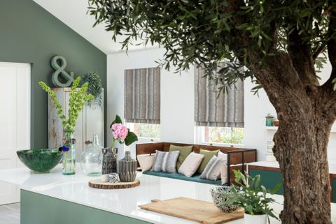 kitchen with a tree in the middle and grey roman blinds at the window