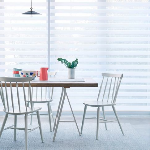 A close up of a white Day & Night blind in a kitchen with a table