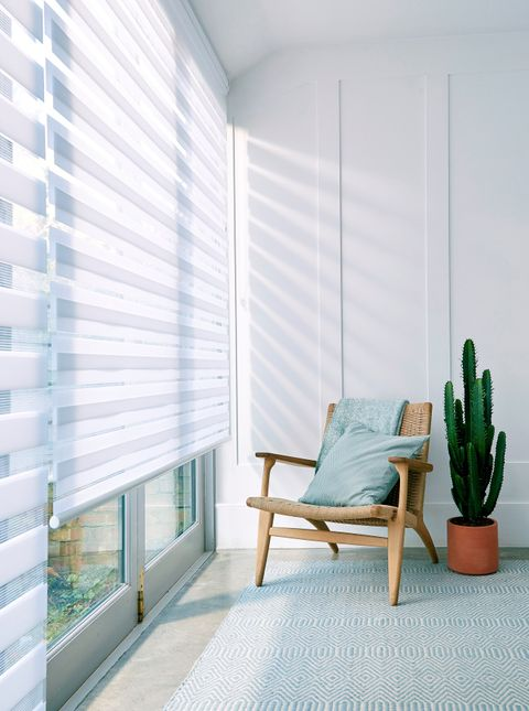 A wide window featuring a white Day & Night roller blinds and a chair
