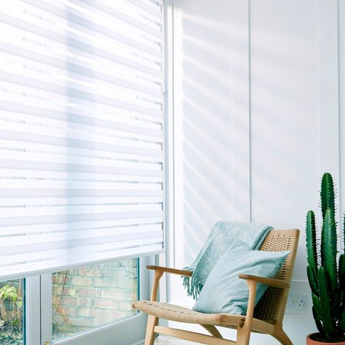 A close up of a white Day & Night blind in a room covering a wide window