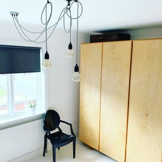 Bedroom corner, wooden wordrobes with hanging black corded lights with a grey roller blind