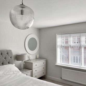 Grey and white bedroom, featuring white wooden venetian blinds with white tape