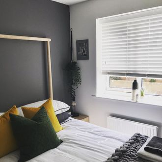 Grey tonal bedroom with yellow cushions and knitted blanket, white wooden ventian blinds