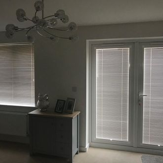 Perfect fit grey venetian blinds on doors and windows in lounge