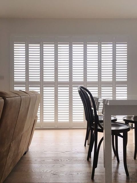 white tracked shutters in dining room