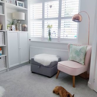 White shutters in living room with pink chair and grey storage chair
