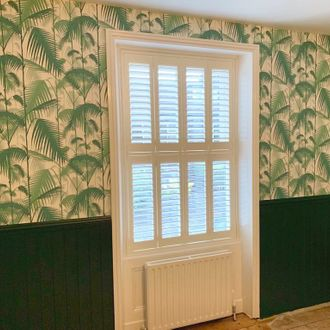 white shutters on windows and wall decorated with palm print wall paper
