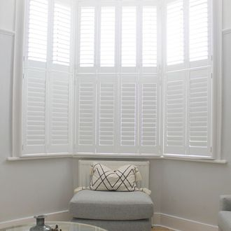 White tier on tier shutters in white living room with grey sofa and round glass table