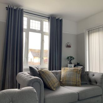 Windows in living room dressed with grey curtains behind grey sofa and side wall windows dresses with vertical blinds