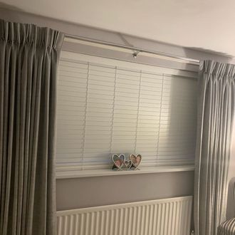 Grey curtains over venetian blinds in a bedroom