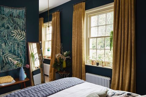 textured shimmering gold curtains hanging on double hung window in blue bed room