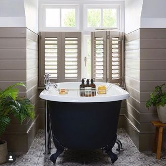 Brown shutters in a bathroom decorated with brown tiles