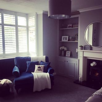 windows dressed with white shutters in a living room where blue sofa chair has been placed infront of windows, and natural light is coming in the room