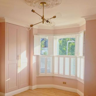 white tier on tier shutters with tilt bars in pink bed room