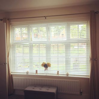 white wooden blinds and gold curtains hanging on windows in living room