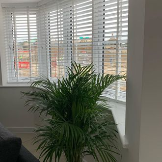 white wooden blinds hanging on bay windows of living room