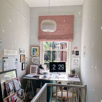 pink roman blinds hanging on window of home office